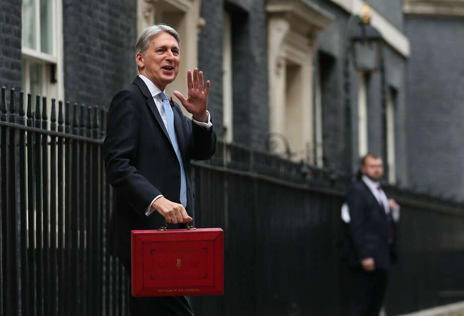 Philip Hammond waves as he holds the Budget Box before heading to Parliament. Photo: Daniel Leal-Olivas / AFP / Getty Images