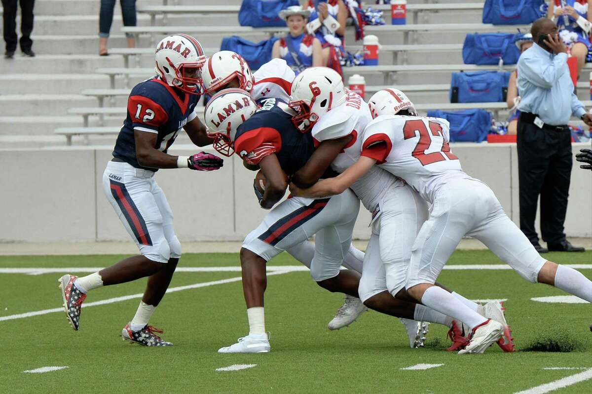 Alex Hogan (9) of Lamar is tackled by Rodney Dansby (6) and Walter Truitt (22) of Bellaire on a punt return in the second quarter of a high school football game between the Lamar Texans and the Bellaire Cardinals on Saturday, October 20, 2018 at Delmar Stadium, Houston, TX.