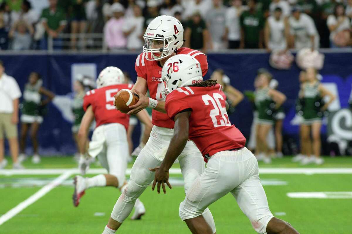 Quarterback Peyton Matocha (4) of St. Thomas hands off to Ian Wheeler (26) in the second quarter of a high school football game between the Strake Jesuit Crusaders and the St. Thomas Eagles on Friday, August 31, 2018 at NRG Stadium, Houston, TX.