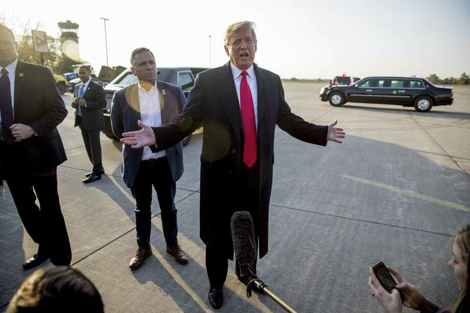 President Donald Trump, accompanied by Rep. Mike Bost, R-Ill., center left, speaks to reporters about a shooting at a Pittsburgh synagogue as he arrives at Southern Illinois Airport in Murphysboro, Ill., Saturday, Oct. 27, 2018, for a rally. Photo: Andrew Harnik, STF / Associated Press / Copyright 2018 The Associated Press. All rights reserved