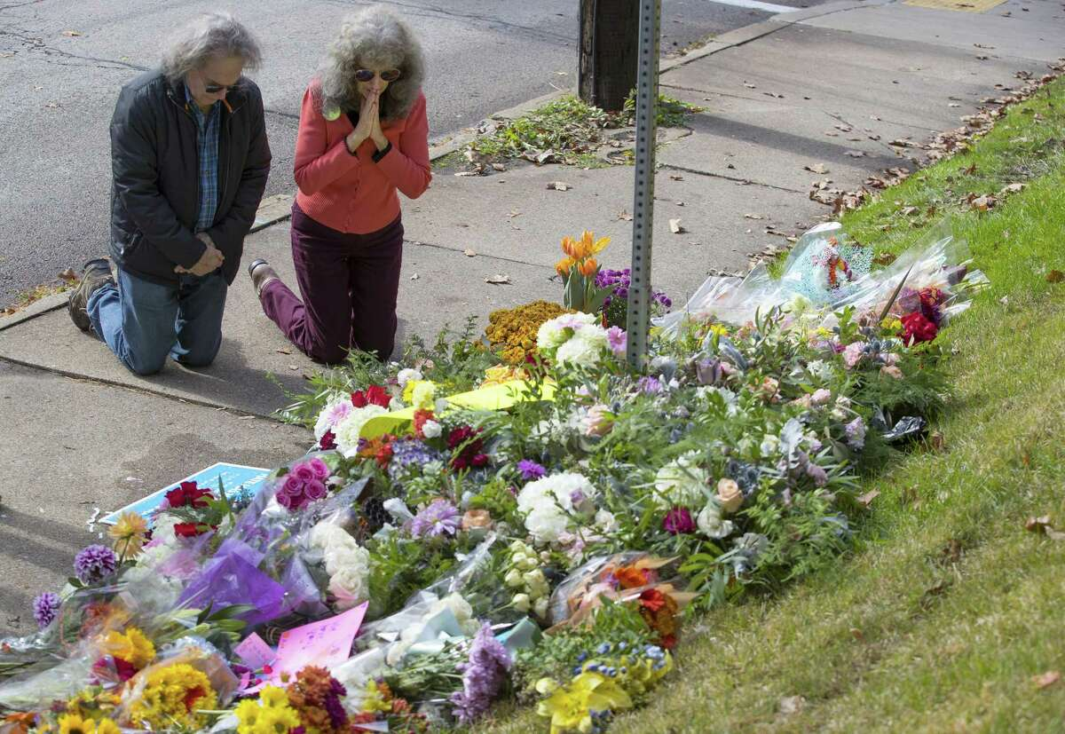 A couple kneels before a memorial at Murray and Wilkins avenues on Sunday, Oct. 28, 2018 in Pittsburgh, Pa. The memorial was for the 11 people that were killed at the shooting at the Tree of Life Synagogue. (Charles Fox/Philadelphia Inquirer/TNS)