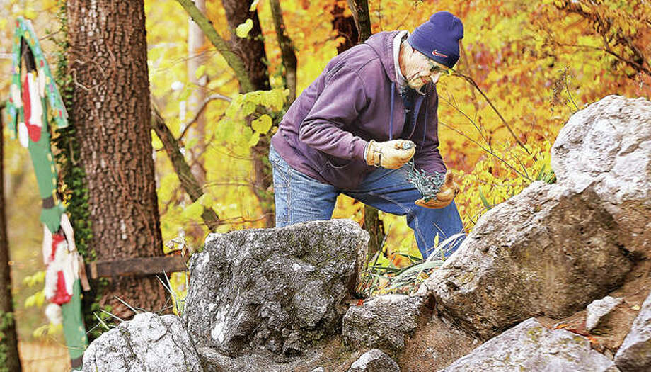 "In this photo from last fall, a member of the Grandpa Gang works on lighting the waterfall in Rock Spring Park in Alton for the annual Christmas Wonderland light display. Like in previous years, the display was vandalized again this year, but Alton Mayor Brant Walker said Monday the lights ""will go on"" despite the theft. Photo: John Badman 