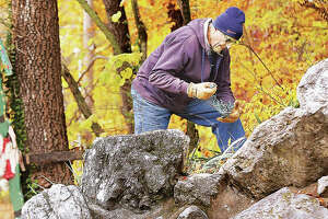 "In this photo from last fall, a member of the Grandpa Gang works on lighting the waterfall in Rock Spring Park in Alton for the annual Christmas Wonderland light display. Like in previous years, the display was vandalized again this year, but Alton Mayor Brant Walker said Monday the lights ""will go on"" despite the theft."