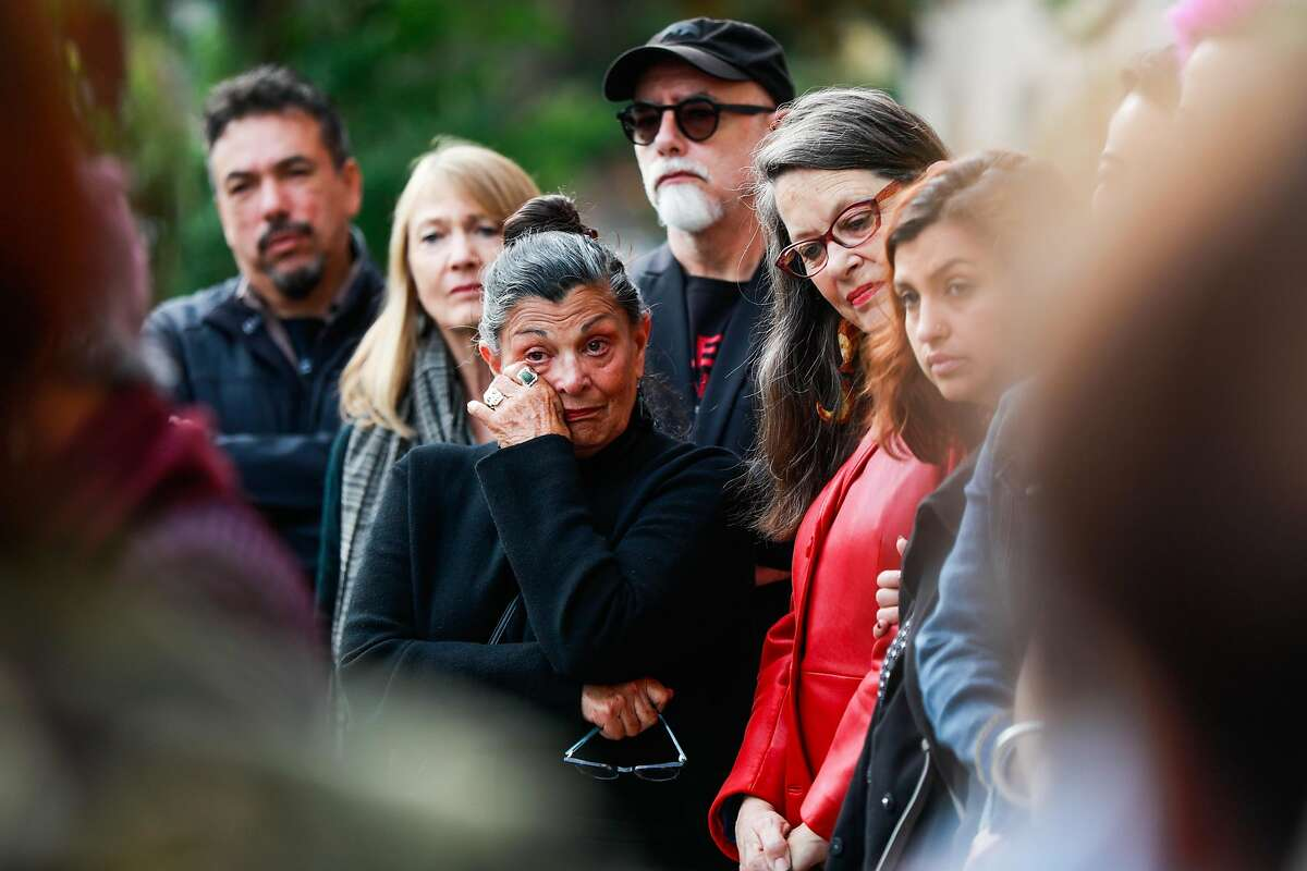 Maria Pinedo (center) wipes her eye as she listens during a press conference regarding the possible eviction of the longtime Mission cultural spot Galeria de la Raza in San Francisco, California, on Monday, Oct. 29, 2018.