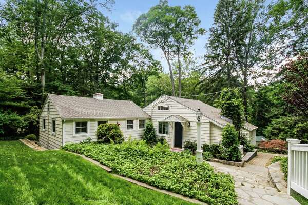 The antique white-colored cottage at 441 Westport Turnpike (Route 136) is nestled in a level and sloping property of almost a half an acre in the Greenfield Hill neighborhood near Brett Woods Open Space.
