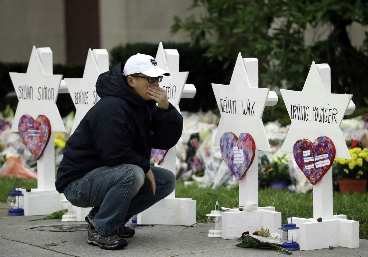 A person pauses in front of Stars of David with the names of those killed in a deadly shooting at the Tree of Life Synagogue, in Pittsburgh, Monday, Oct. 29, 2018. (AP Photo/Matt Rourke)