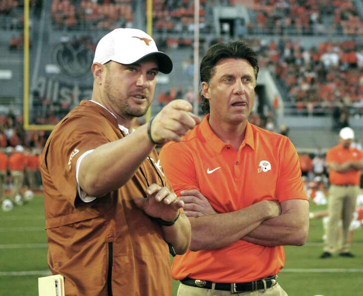 Texas head coach Tom Herman, left, and Oklahoma State head coach Mike Gundy talk prior to an NCAA college football game in Stillwater, Okla., Saturday, Oct. 27, 2018. (AP Photo/Brody Schmidt)