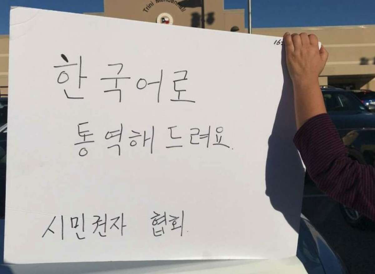 """Volunteers on Sunday held a sign that translates """"Korean language available,?"""" at early voting location in west Houston."""