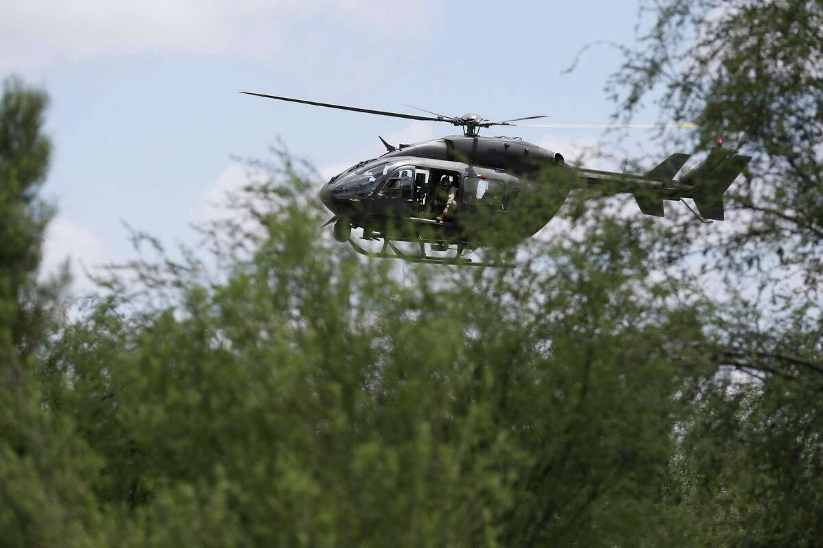 A Texas National Guard helicopter provides air support as U.S. Border Patrol agents search for immigrants near the Anzalduas International Bridge in Mission last May. The president's order to send active duty troops, coming eight days before the midterm elections, will add to the guard presence and bring the total number of troops to just under 7,300.