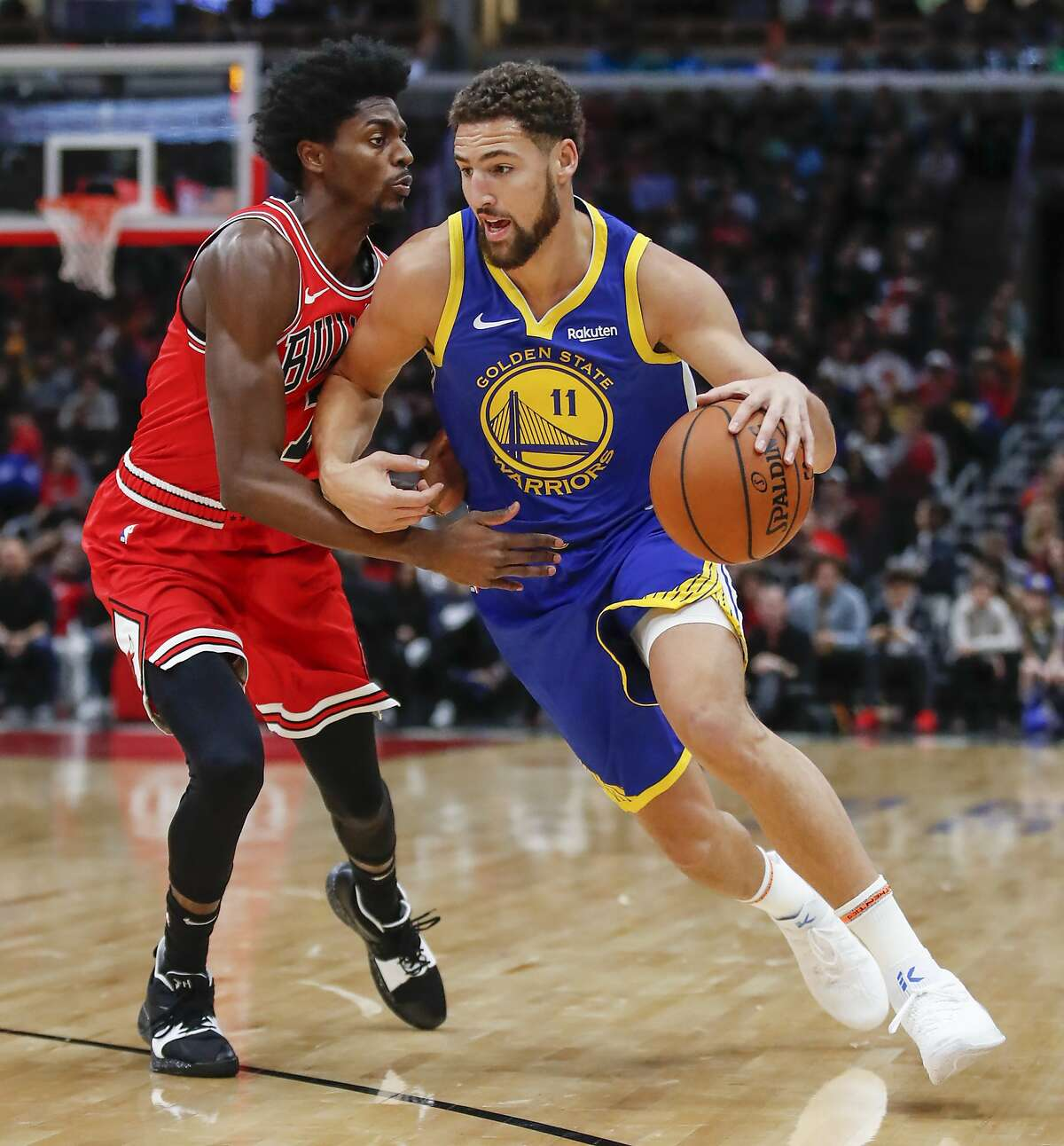 Golden State Warriors guard Klay Thompson, right, drives to the basket against Chicago Bulls forward Justin Holiday, left, during the first half of an NBA basketball game, Monday, Oct. 29, 2018, in Chicago. (AP Photo/Kamil Krzaczynski)