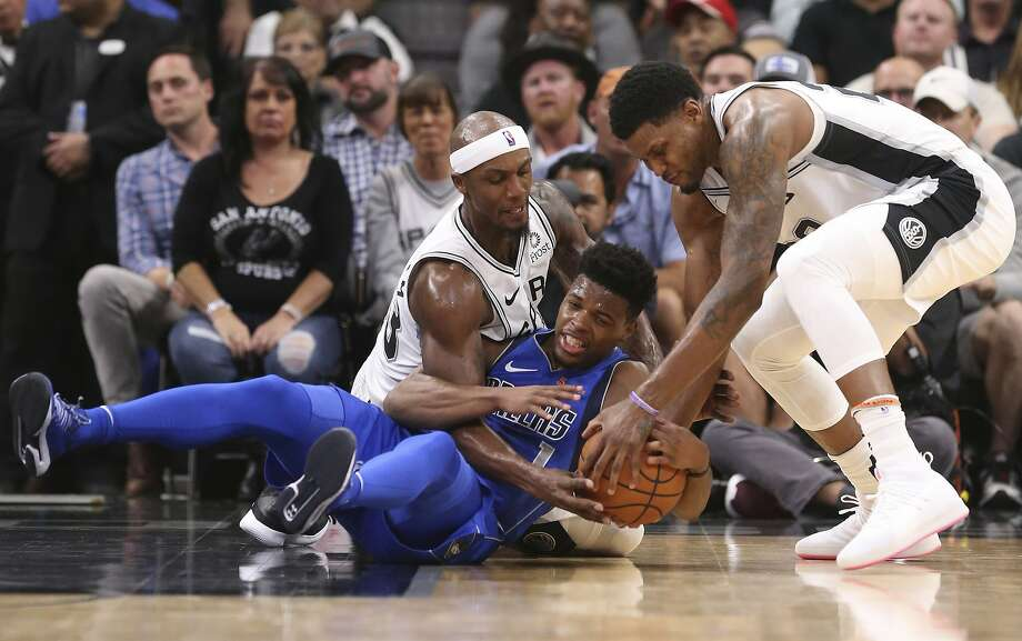 San Antonio Spurs' Dante Cunningham and Rudy Gay scramble for the ball against Dallas Mavericks' Dennis Smith Jr. during the first half at the AT&T Center, Monday, Oct. 29, 2018. Photo: JERRY LARA, San Antonio Express-News