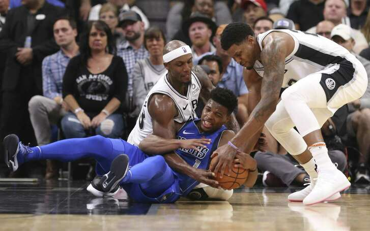 San Antonio Spurs' Dante Cunningham and Rudy Gay scramble for the ball against Dallas Mavericks' Dennis Smith Jr. during the first half at the AT&T Center, Monday, Oct. 29, 2018.