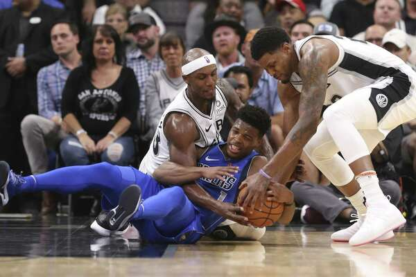San Antonio Spurs?' Dante Cunningham and Rudy Gay scramble for the ball against Dallas Mavericks?' Dennis Smith Jr. during the first half at the AT&T Center, Monday, Oct. 29, 2018.