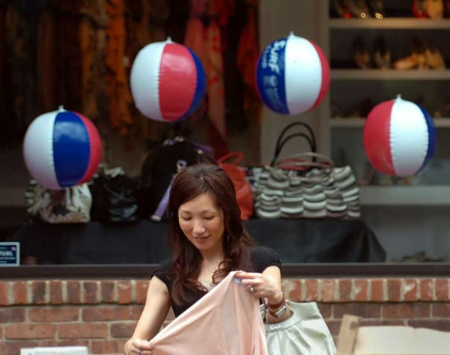 Yukiko Takai of Mamaroneck, N.Y., does some Sidewalk Sale Days shopping at the tables of the Women's Guild of St. Mary Church on Greenwich Avenue, Thursday afternoon, July 15, 2010. Photo: Bob Luckey / Greenwich Time
