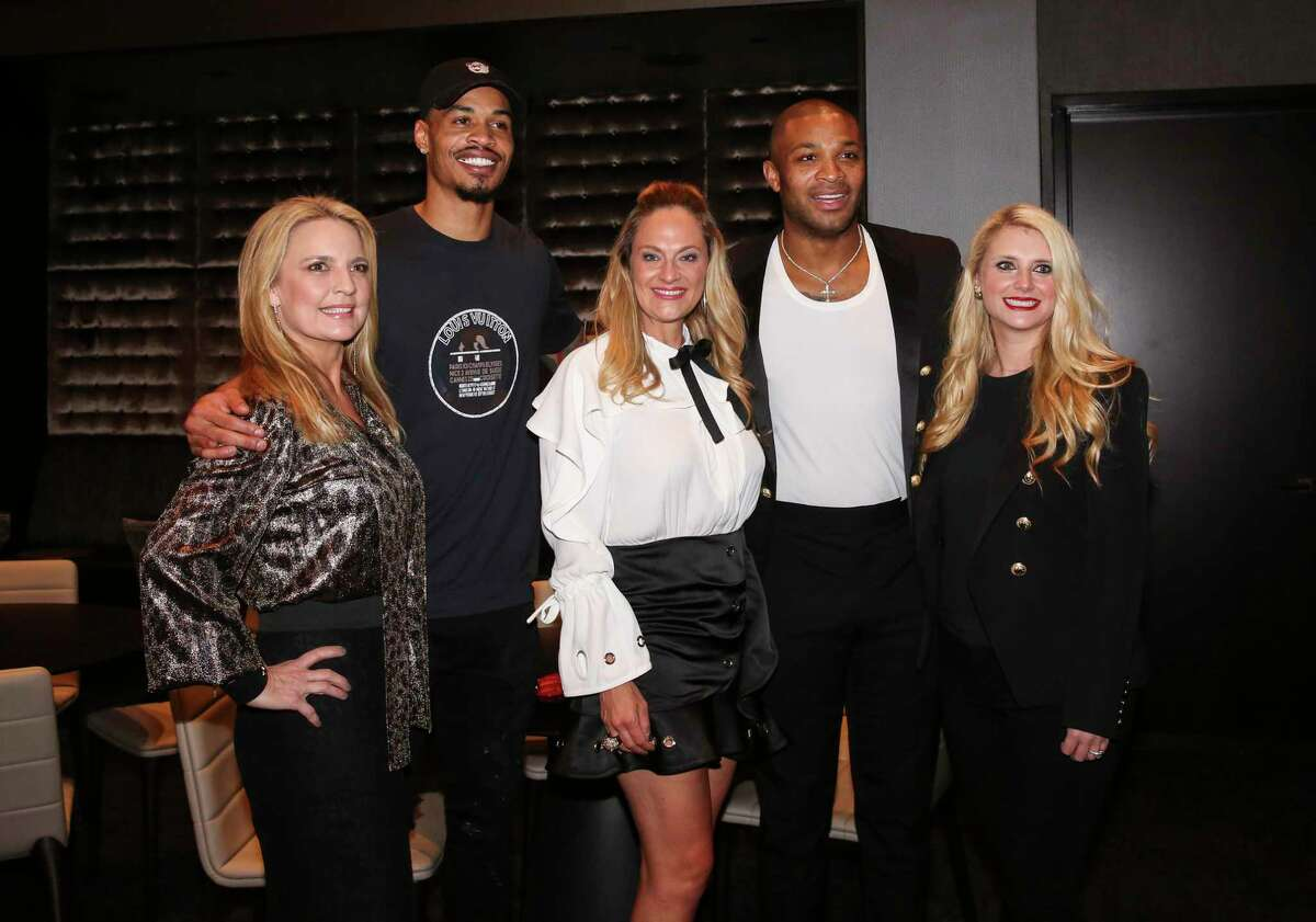 Co-chairs Melissa Juneau, from left, Rachel Regan and Christine Falgout pose for a photograph with Houston Rockets players Gerald Green and P.J. Tucker at the Lexus Lounge before the MVPs courtside dinner, hosted by Houston Rockets and Children's Memorial Hermann, at Toyota Center on Thursday, Oct. 25, 2018, in Houston.