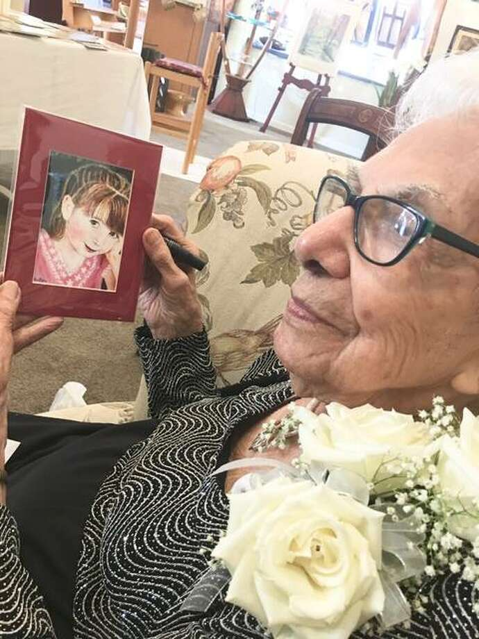 """This little girl, she had something, they knew she wouldn't live, I painted her portrait,"" Virginia ""Gini"" Leitner, 103, of St. Charles, Missouri, said about the painting she holds at Von Dell Gallery in Wood River, Illinois, where she had a solo exhibit last month. Photo: Jill Moon