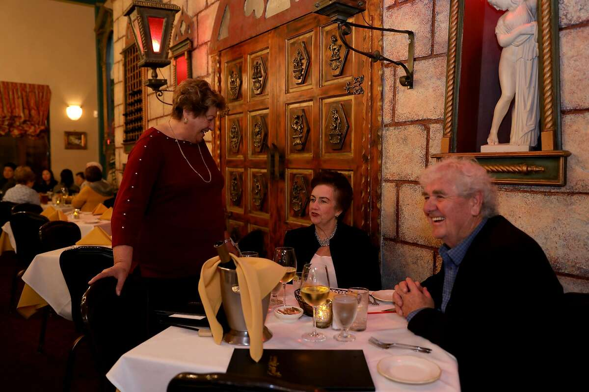 """Co-founder Josephine Di Grande converses with Sheila and George Birmingham at Gold Mirror in San Francisco, Calif., on Saturday, October 20, 2018. The couple has been dining at the establishment for 45 years. """"We've never had a bad meal here,"""" George Birmingham said. The Italian restaurant, located at 800 Taraval St., will soon celebrate its 50th anniversary."""