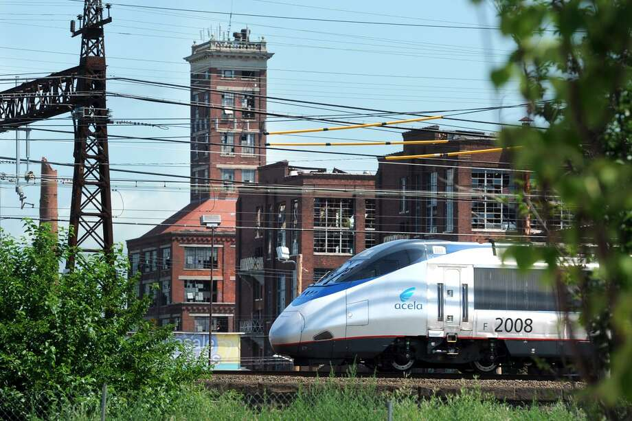 An Amtrak Acela train passes near Crescent Crossing, a new affordable housing development in Bridgeport, Conn. July 18, 2017. Photo: Ned Gerard / Hearst Connecticut Media / Connecticut Post