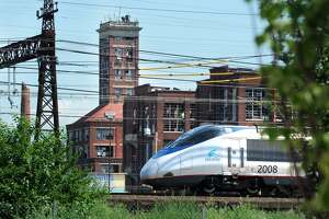 An Amtrak Acela train passes near Crescent Crossing, a new affordable housing development in Bridgeport, Conn. July 18, 2017.