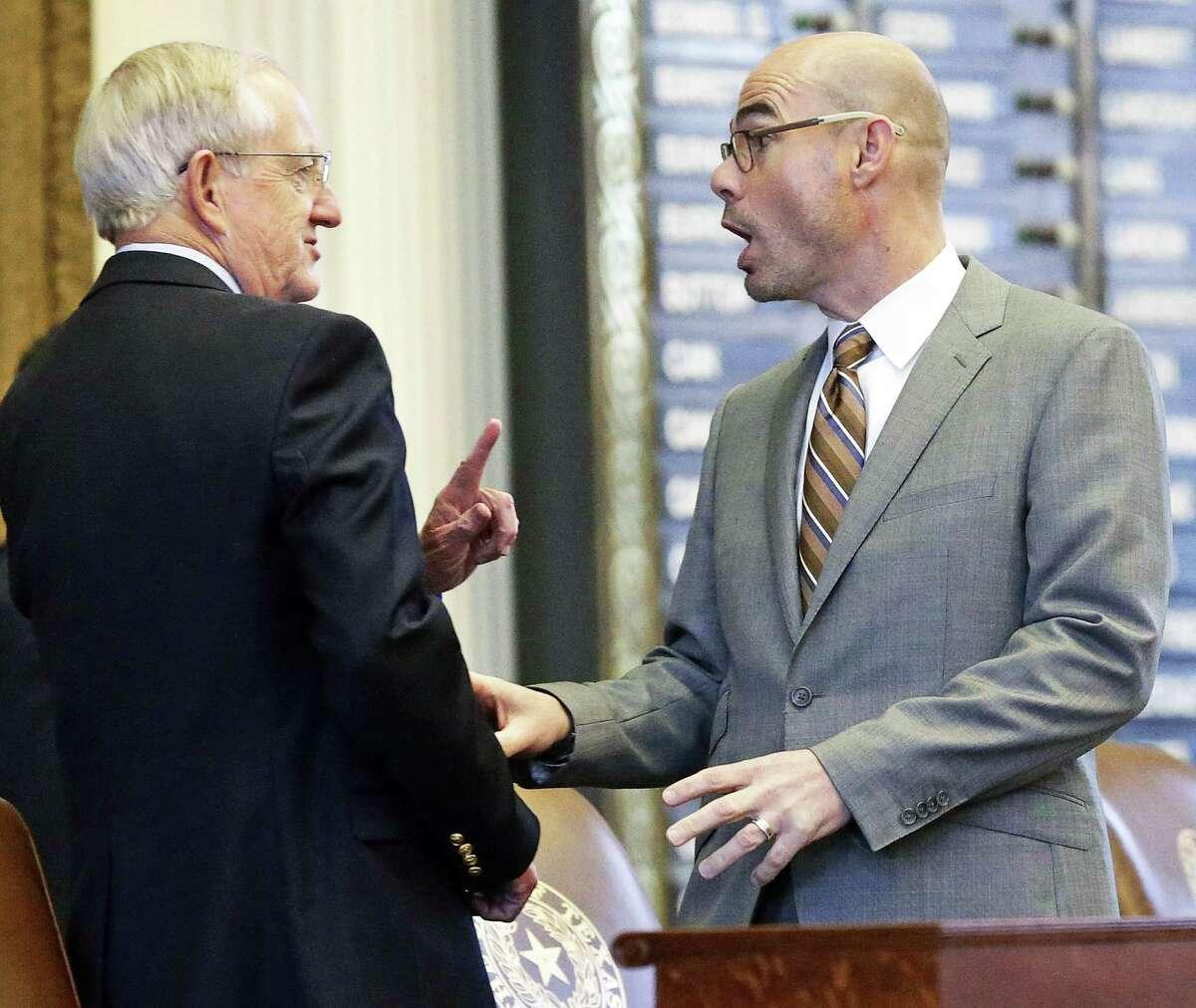 Represetative Dennis Bonnen, R-Angleton, (right) engages with Representative John Smithee, R-Amarillo, as members debate legislation in the House of Representatives on April 27, 2017.