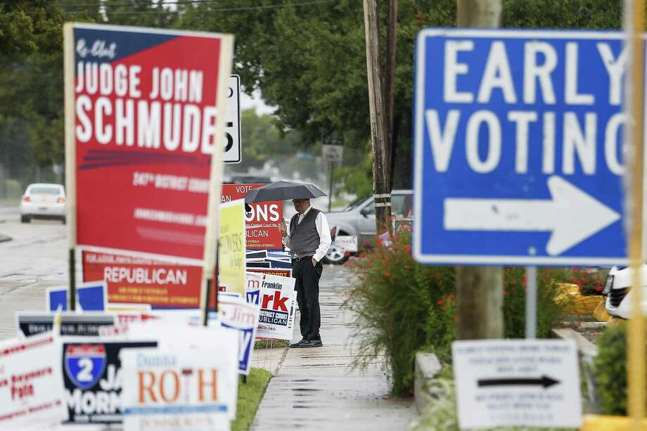 A man walks past campaign signs as people brave the rain to head to the polls for the second day of early voting at the Trini Mendenhall Community Center Tuesday Oct. 23, 2018 in Houston. Photo: Michael Ciaglo, Houston Chronicle / Staff Photographer / Michael Ciaglo