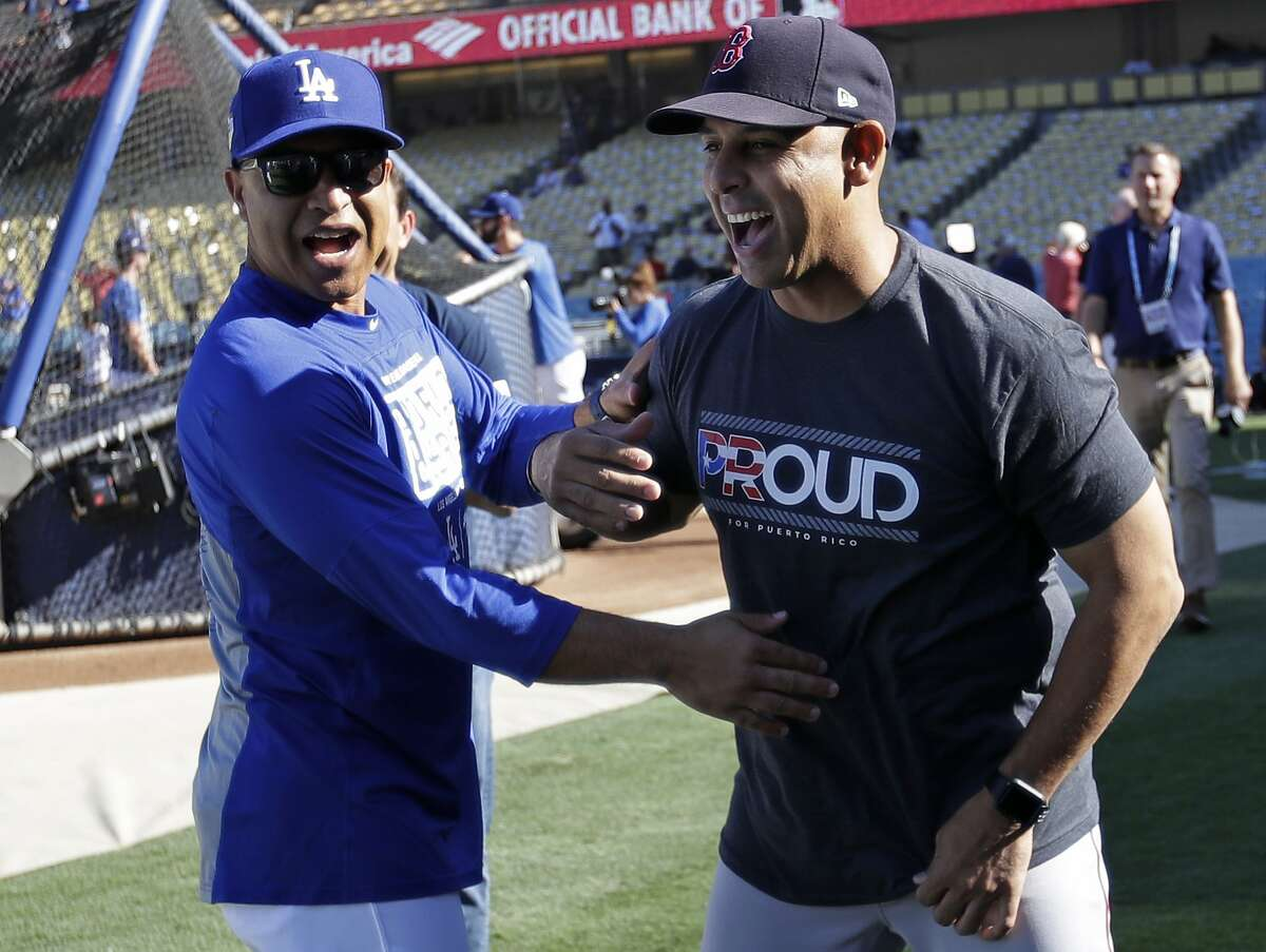 Los Angeles Dodgers manager Dave Roberts, left, jokes with Boston Red Sox manager Alex Cora during batting practice before Game 4 of the World Series baseball game on Saturday, Oct. 27, 2018, in Los Angeles. (AP Photo/David J. Phillip)