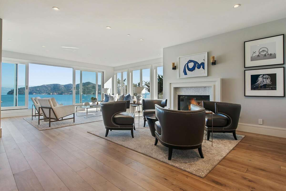 A gas fireplace with stone surround warms a living room with views of Belvedere Cove.