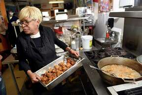 Patricia Deroche, co-owner of Patty's Caribbean Cuisine, prepares fried chicken for a buffet lunch after a ribbon cutting at the new restaurant on Congress Avenue in New Haven on October 30, 2018.