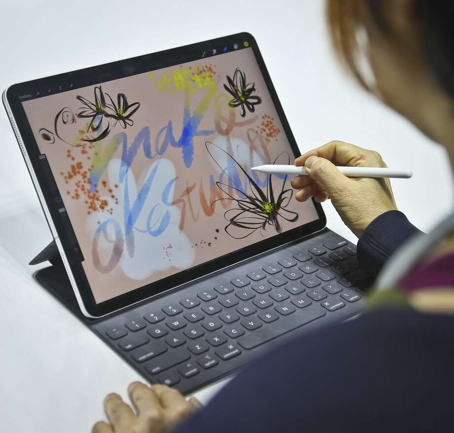 Japanese artist Mako Oke uses a new iPad Pro after an event announcing updated products in New York. Photo: Bebeto Matthews / Associated Press