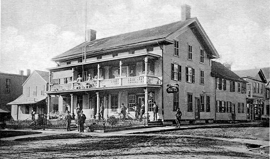 "A business and architectural anchor of the village of New Milford during the latter years of the 19th century was the New England House Hotel, located at the southeast corner of Main and Bank streets. Above, a photograph likely from the 1880s depicts a quiet day in town as patrons of the hotel and perhaps some local residents capitalize on their ideal vantage point to check out what's going on in the village. The hotel and all the wooden buildings around it were destroyed during the Great Fire of May, 1902. If you have a ""Way Back When"" photograph to share, contact Deborah Rose at drose@newstimes.com or 860-355-7324. Photo: Courtesy Of Gary Scribner / The News-Times Contributed"