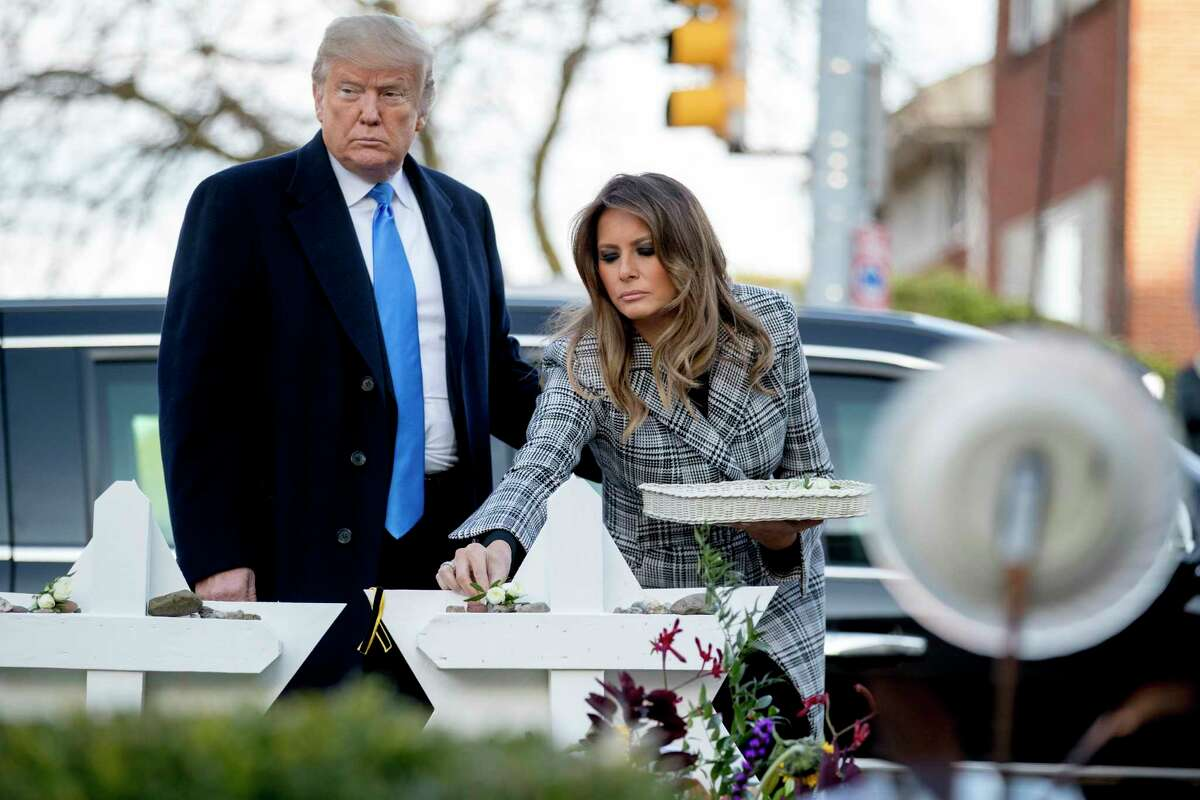 First lady Melania Trump, accompanied by President Donald Trump, puts down a white flower at a memorial for those killed at the Tree of Life Synagogue in Pittsburgh, Tuesday, Oct. 30, 2018.