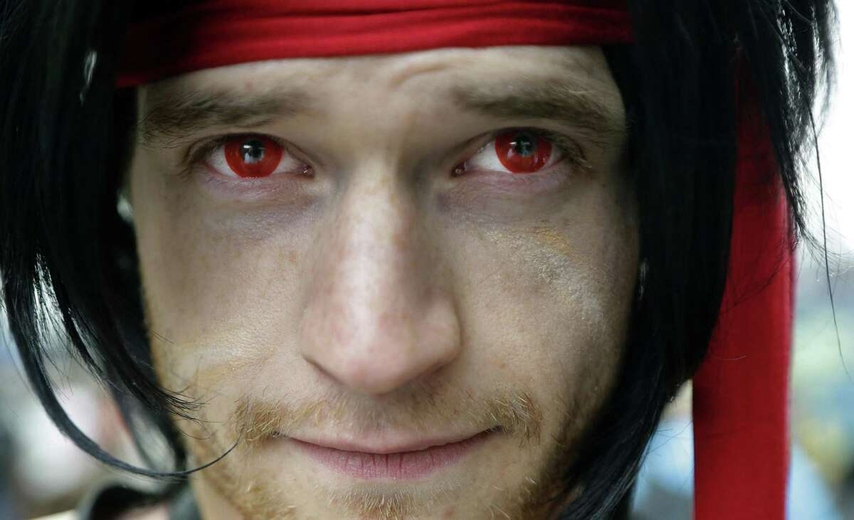 """David O'Rourke, of Portland, Ore., an attendee at the Penny Arcade Expo in Seattle, poses for a photo Friday, Aug. 29, 2014, with his red-colored contact lenses that are part of his costume for the character """"Jecht"""" from the Final Fantasy 10 video game."""