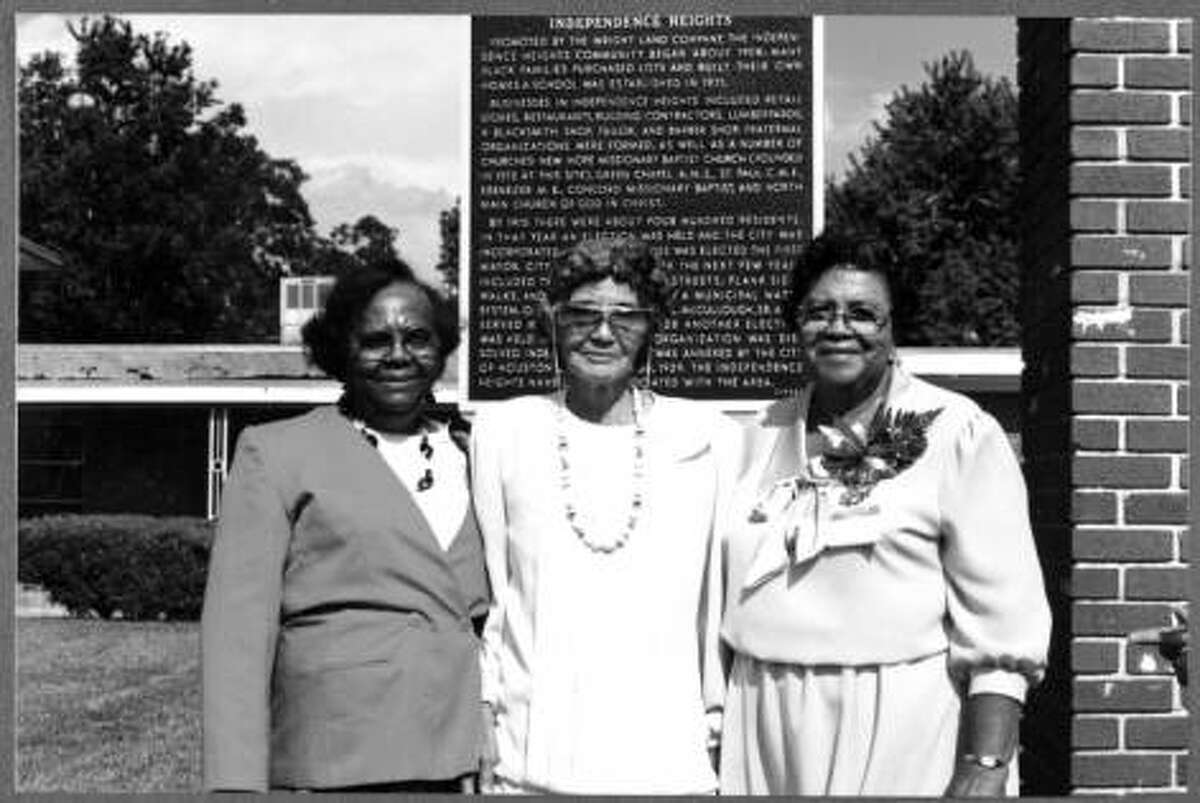 On the grounds of Greater New Hope Missionary Baptist Church, Lota McCullough Charles, Leona Wills, and Vivian Hubbard Seals stand in front of a Texas Historical Commission Marker detailing the history of Independence Heights.
