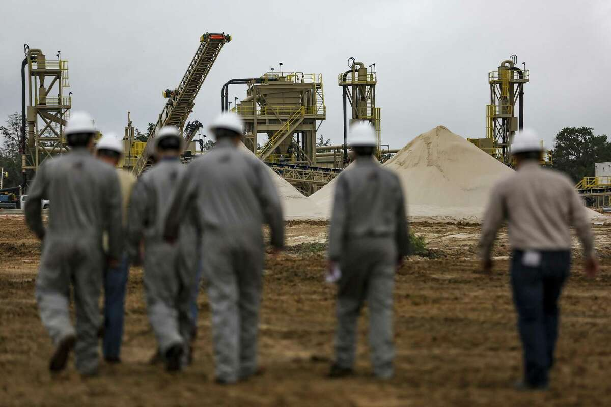 WildHorse Resource Development employees walk out toward piles of sand from their mine they are developing Tuesday Oct. 2, 2018 in Caldwell. (Michael Ciaglo/Houston Chronicle via AP)
