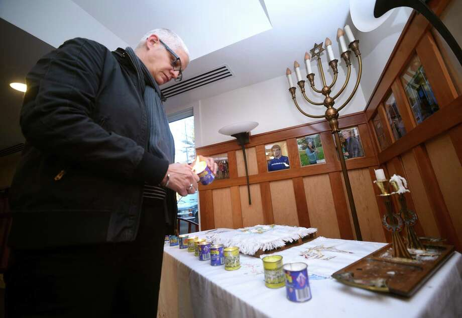Associate professor of journalism Margarita Diaz lights a candle for one of the eleven victims of the shooting at the Tree of Life synagogue in Pittsburgh during a mourning service at the Hereld House for Jewish Life at Quinnipiac University in Hamden on October 30, 2018. Photo: Arnold Gold / Hearst Connecticut Media / New Haven Register
