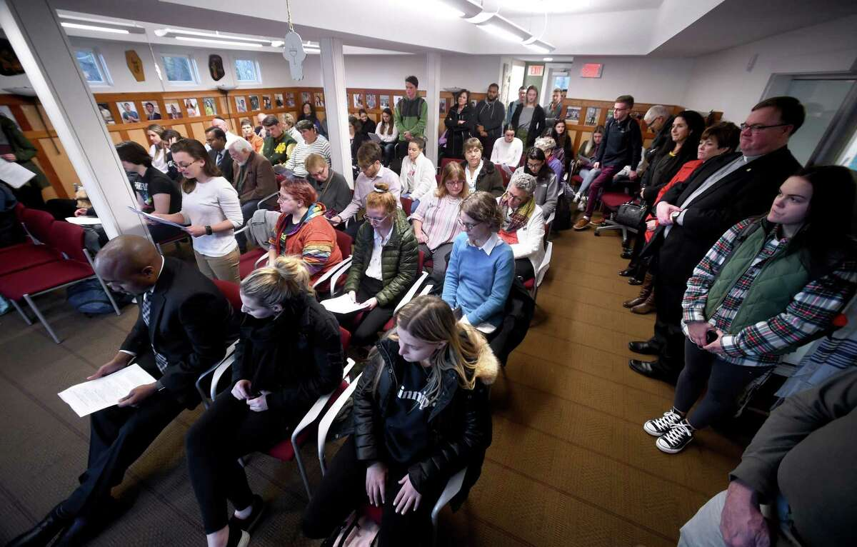 Quinnipiac University senior Tovah Williamson (left) stands for a reading during a mourning service for the eleven victims of the shooting at the Tree of Life synagogue in Pittsburgh at the Hereld House for Jewish Life at Quinnipiac University in Hamden on October 30, 2018.