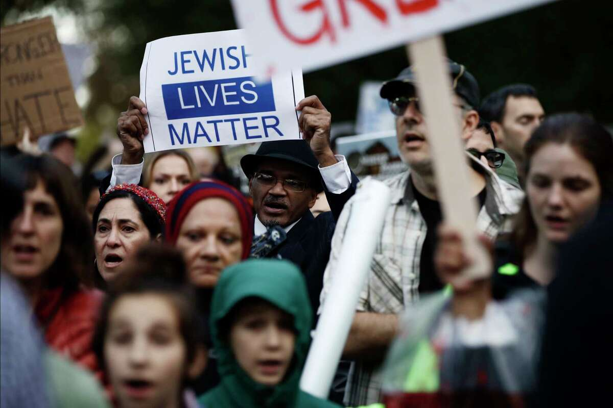 Protesters demonstrate near Pittsburgh's Tree of Life Synagogue where President Donald Trump and first lady Melania Trump were visiting a memorial in Pittsburgh, Tuesday, Oct. 30, 2018. The Trumps came to Pittsburgh to honor the victims of a mass shooting at the synagogue last week.