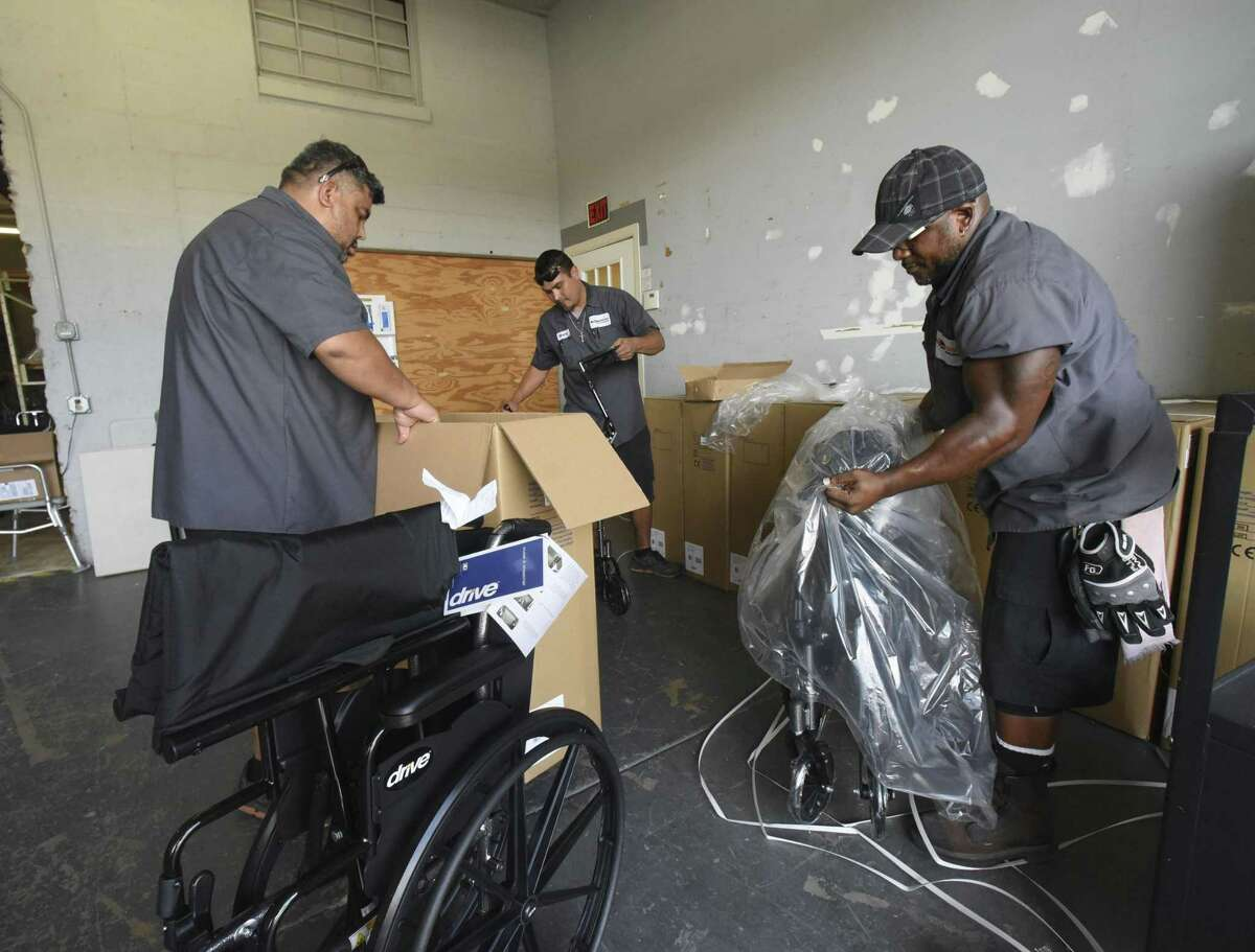 Rick Garza, left, Mario Ochoa and Manuel Becker unpacked supplies at Project MEND on Aug. 15, 2018. The nonprofit provides refurbished medical equipment and assistive technology to people with disabilities who can't afford the equipment or whose insurance won't cover it.
