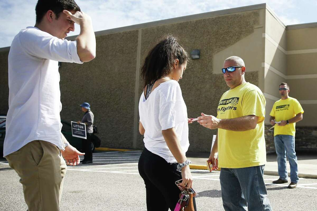 """Houston Firefighter Nick Buonarosa campaigns for people to vote for Proposition B, the ballot referendum that would grant firefighters pay """"parity"""" with police officers of corresponding rank and seniority, during early voting at Trini Mendenhall Community Center Friday, Oct. 26, 2018, in Houston."""