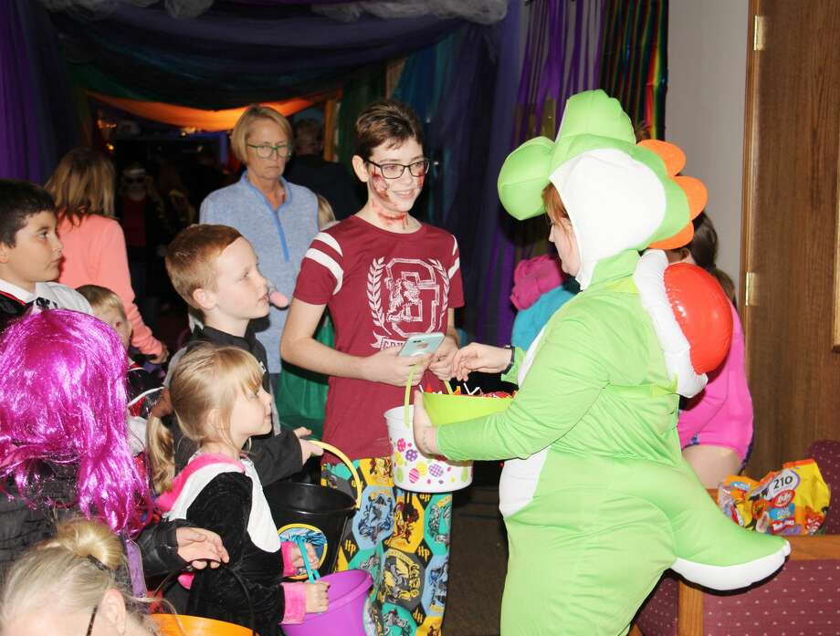 One of Nintendo's most famous characters — Yoshi — was spotted handing out candy to dozens of trick-or-treaters Tuesday night. More than 500 kids packed into Evangel Life Assembly of God Church for the 10/30 Party — an annual indoor trick-or-treat event. Various rooms throughout the church replicated video game scenes as well as some surprises by a few characters. Photo: Bradley Massman/Huron Daily Tribune