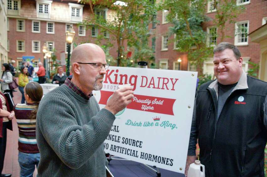 Douglas Porter, left, food service director for Ravena Caymans Selkirk school district gets a taste of chocolate milk from King Farm's Jan King during the Capital Region Food and Farms Business Expo Tuesday Oct. 30, 2018 in Colonie, NY. (John Carl D'Annibale/Times Union)