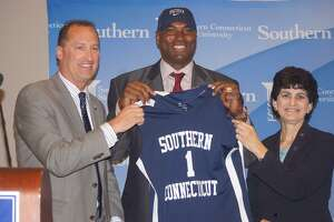 Southern Connecticut State coach Scott Burrell, center, poses with athletic director Jay Moran and president Mary Papazian in July 2015.