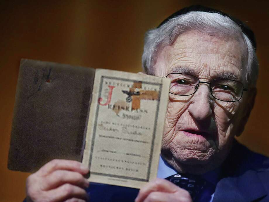 "New Haven resident and Holocaust survivor Isidor ""Izzy"" Juda holds his passport at the Holocaust Remembrance Day at the University of New Haven on April 10, 2018. Photo: Catherine Avalone / Hearst Connecticut Media / New Haven Register"