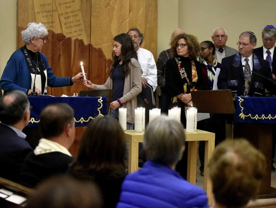 Rabbi Stacy Offner of Temple Beth Tikvah, left, officiates a community vigil Tuesday evening at the Madison temple in remembrance of  the victims of Saturday's Pittsburgh synagogue shooting. Handing Offner a candle is temple member Hannah Mervine, 13, of Madison. Photo: Peter Hvizdak / Hearst Connecticut Media / New Haven Register