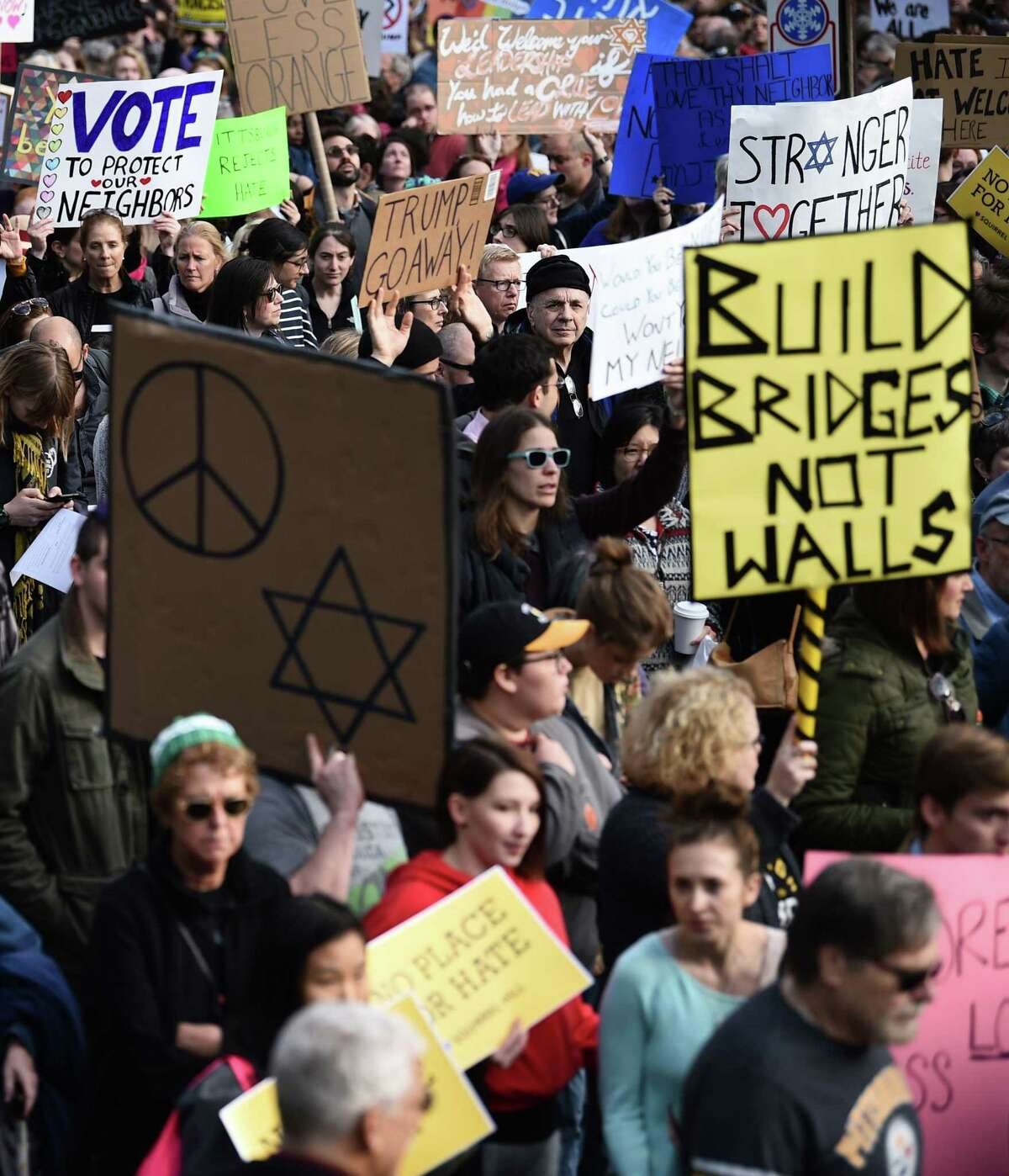 """Scores of protesters took to the streets of Pittsburgh to denounce a visit by President Donald Trump in the wake of a mass shooting at a synagogue that left 11 people dead. Demonstrators gathered near the Tree of Life synagogue, where the shooting took place, holding signs that read """"President Hate, Leave Our State!"""" and """"Trump, Renounce White Nationalism Now."""""""