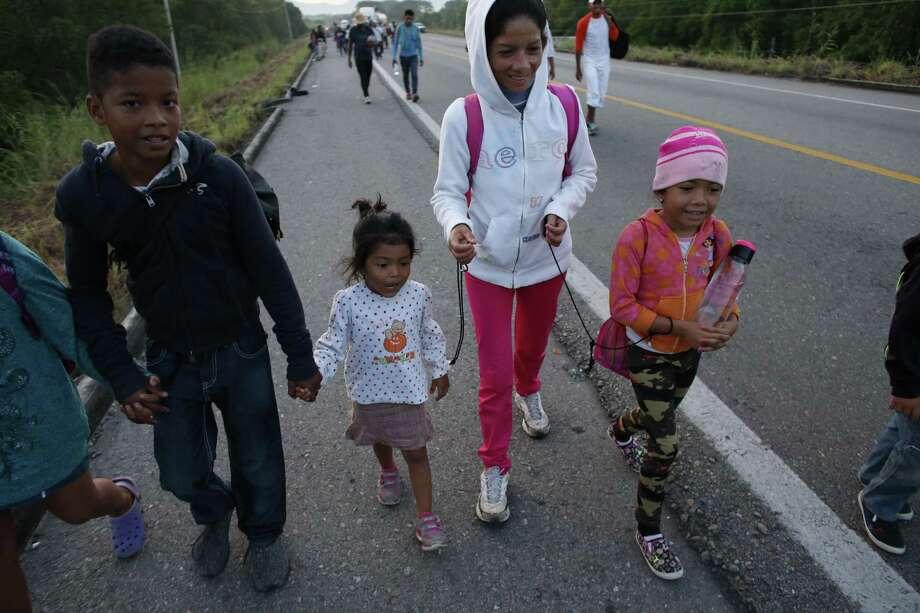 La migrante Fany Lizeth Cruz camina con cuerdas atadas a la muñeca de su hija (derecha) y de otra niña, acompañada por su hijo, en las afueras de Tapanatepec, México, el 29 de octubre de 2018. Photo: Rebecca Blackwell /Associated Press / Copyright 2018 The Associated Press. All rights reserved.