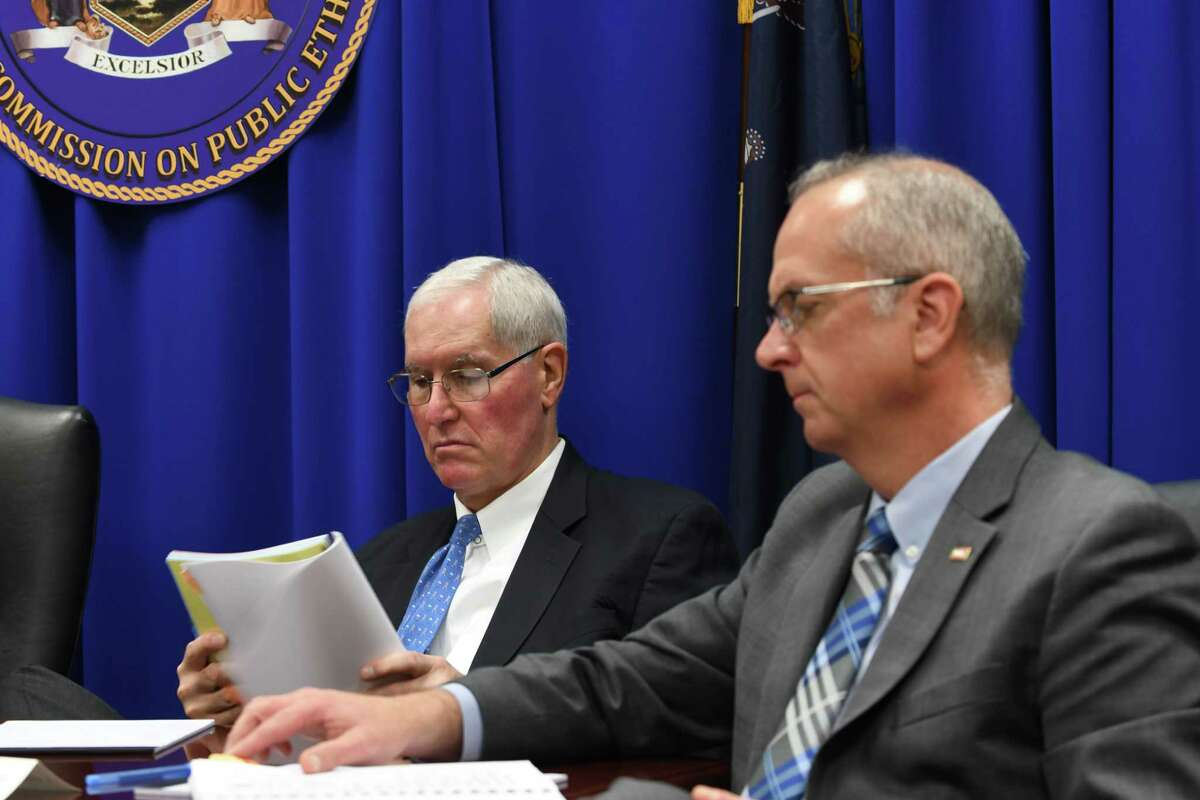 Joint Commission of Public Ethics commissioners, Gary Lavine, left, and Gerard McAuliffe, Jr., right, read the agenda during a JCOPE meeting on Tuesday, Oct. 30, 2018, in Albany, N.Y. (Will Waldron/Times Union)