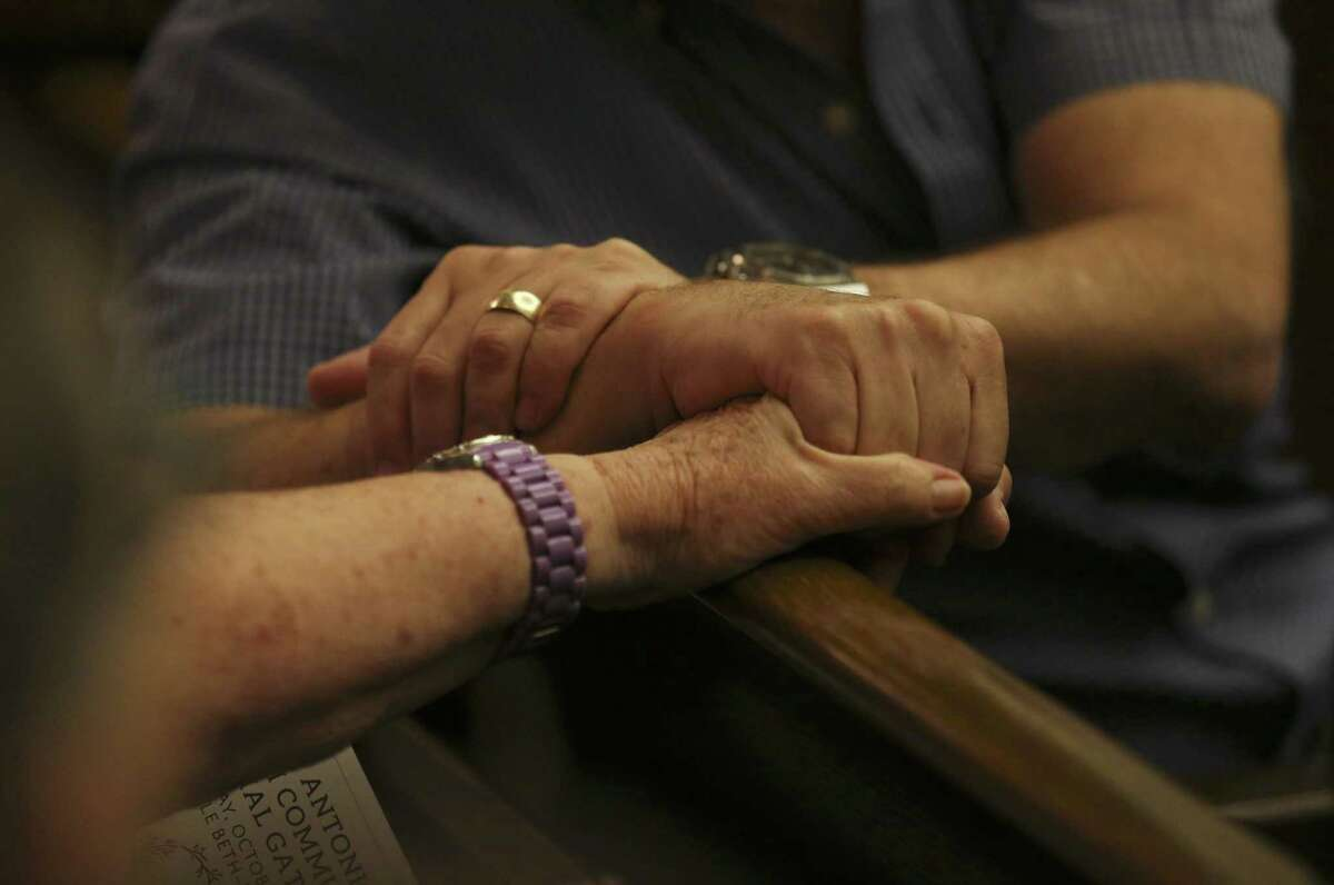 Hands from two people are clasped as Temple Beth-El hosts a memorial in the wake of last weekend's shooting deaths in a Pittsburgh synagogue on Tuesday, Oct. 30, 2018. People from all walks of faith and from the city gathered as the first funerals took place for the 11 Jewish congregants who were gunned down by a deranged anti-semite at the Tree of Life synagogue in Pittsburgh. The San Antonio Jewish community gathered at Temple Beth-El and opened their place of worship to the public to mourn the victims. (Kin Man Hui/San Antonio Express-News)