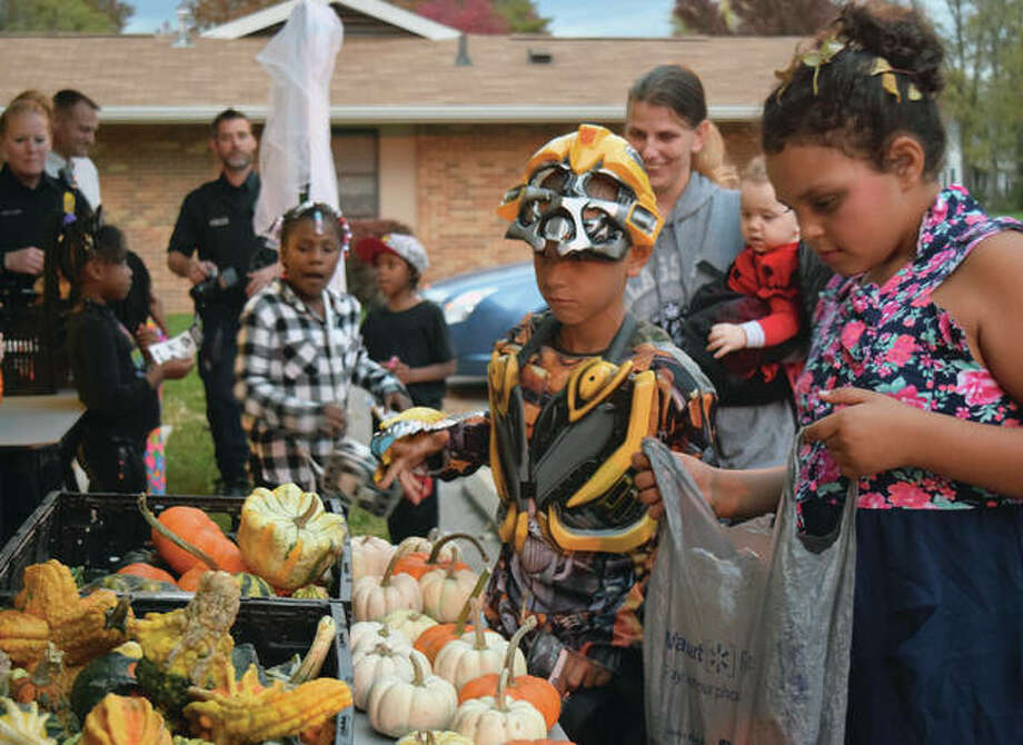 Lashaun Slater, 10, and Mackenzie White, 9, pick out pumpkins at the Jacksonville Police Department substation as part of their trick-or-treating Tuesday. Photo: Audrey Clayton | Journal-Courier