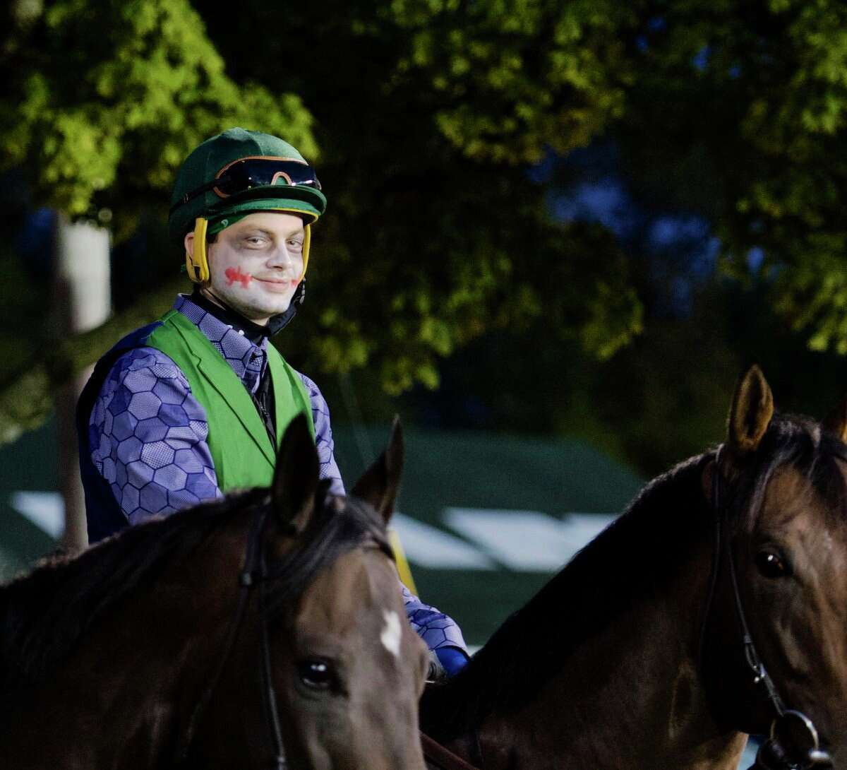 Halloween arrived before sunrise Tuesday at Churchill Downs in Louisville, Ky. Exercise riders Tara Lee and Brody Wilkes galloped in for training dressed up as comic book characters Catwoman and the Joker.
